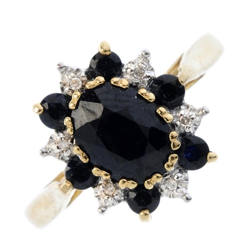 305 - A 9ct gold sapphire and diamond cluster ring. The oval-shape sapphire, within an alternating single-...
