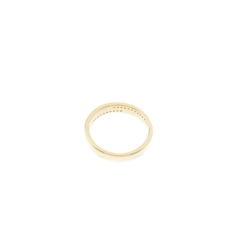 308 - An 18ct gold diamond band ring. Designed as two brilliant-cut diamond off-set lines, channel set to ...