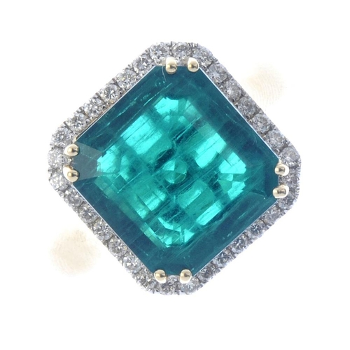 311 - A synthetic emerald and diamond cluster ring. The square-shape synthetic emerald, within a brilliant...
