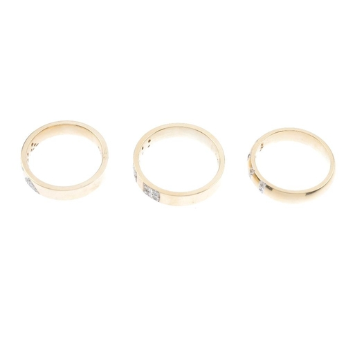 322 - Three 9ct gold diamond band rings. To include a diamond triangular panel ring, a diamond lines band ...