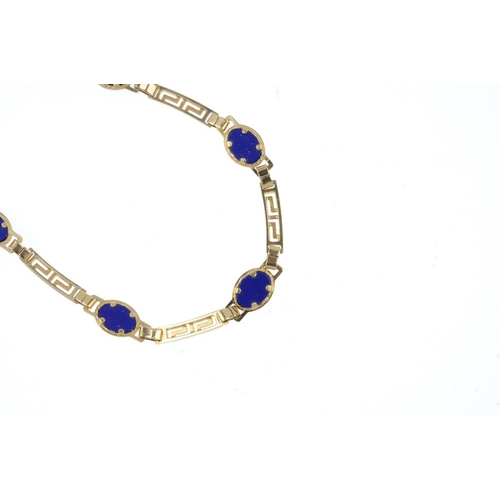 323 - A lapis lazuli necklace. The front designed as oval-shape lapis lazuli cabochons, interspaced by a f...