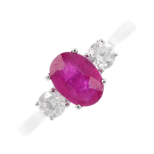 344 - An 18ct gold glass-filled ruby and diamond three-stone ring. The oval-shape glass-filled ruby, with ...