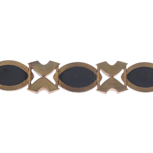 345 - A 9ct gold onyx bracelet. Comprising a series of marquise-shape onyx panels, interspaced by a geomet...