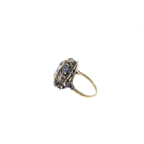 346 - An early 20th century gem-set ring. The replacement oval-shape synthetic spinel, within a bi-colour ...