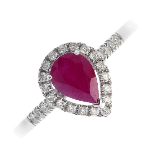 348 - An 18ct gold ruby and diamond cluster ring. The pear-shape ruby, with brilliant-cut diamond surround...