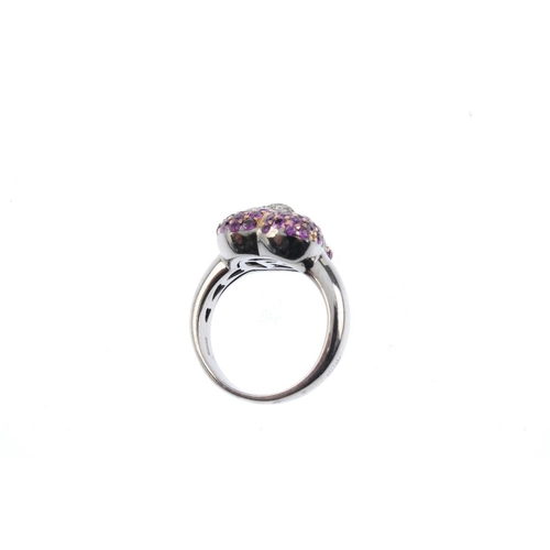 349 - An 18ct gold ruby and diamond ring. Designed as a circular-shape ruby heart, within a brilliant-cut ...