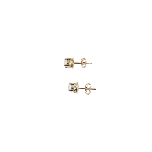 354 - A pair of diamond stud earrings. Each designed as a brilliant-cut diamond, with similarly-cut diamon...
