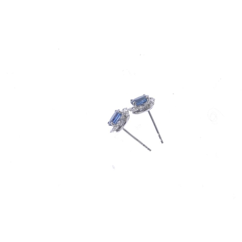 366 - A pair of sapphire and diamond cluster earrings. Each designed as an oval-shape sapphire, within a b...