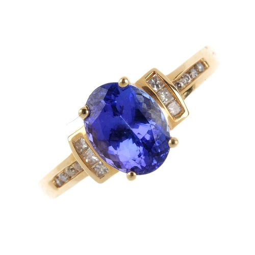 369 - A 14ct gold tanzanite single-stone ring. The oval-shape tanzanite, with square-shape diamond line si...