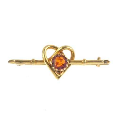 373 - An early 20th century 9ct gold citrine brooch. The circular-shape citrine, within an intertwined hea...