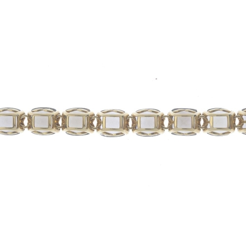 389 - A smoky quartz bracelet. Designed as a series of oval-shape smoky quartz links, with partially conce...