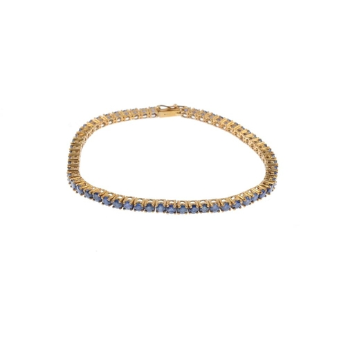 392 - A 9ct gold sapphire bracelet. The circular-shape sapphire line, with push-piece clasp. Hallmarks for...