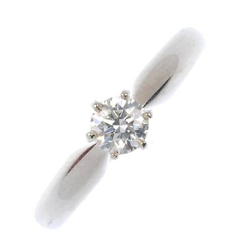 394 - An 18ct gold diamond single-stone ring. The brilliant-cut diamond, with tapered shoulders and plain ...