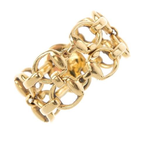 413 - GUCCI - an 18ct gold dress ring. Of openwork design, comprising two stylised stirrup lines. AF. Sign...