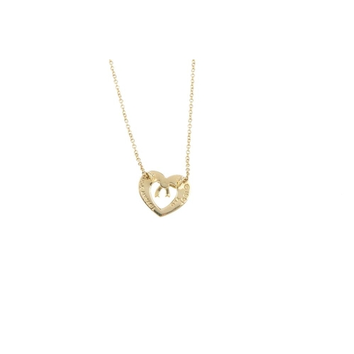 417 - TIFFANY & CO- an 18ct gold pendant. Designed as a stylised bow, set atop the openwork heart, with in...