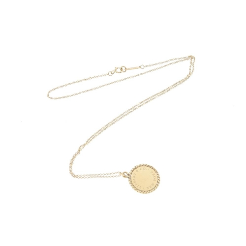 424 - TIFFANY & CO. - an 18ct gold pendant. The 'Tiffany & Co New York' disc, within a rope-twist surround...