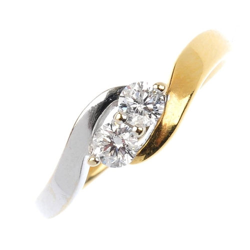 427 - An 18ct gold diamond two-stone crossover ring. Of bi-colour design, the brilliant-cut diamonds, with...