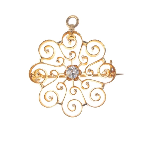 430 - A diamond brooch.  Of openwork design, the old-cut diamond, within a scrolling surround. May also be...