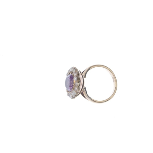 432 - An amethyst and split pearl cluster ring. The oval-shape foil-back amethyst, within a split pearl su...