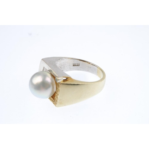435 - A cultured pearl and diamond dress ring. Of bi-colour design, the cultured pearl, with polished and ...