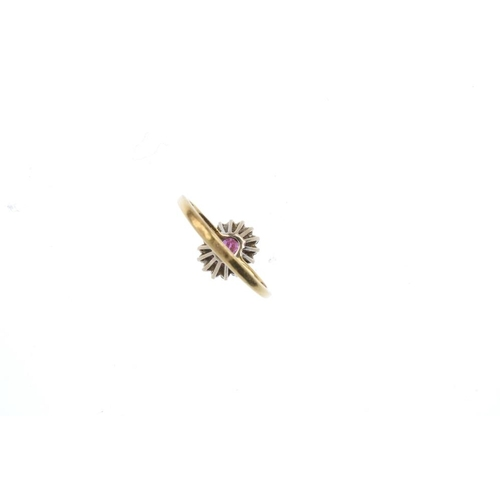 437 - A ruby and diamond cluster ring. The oval-shape ruby, within a brilliant-cut diamond surround. Total...
