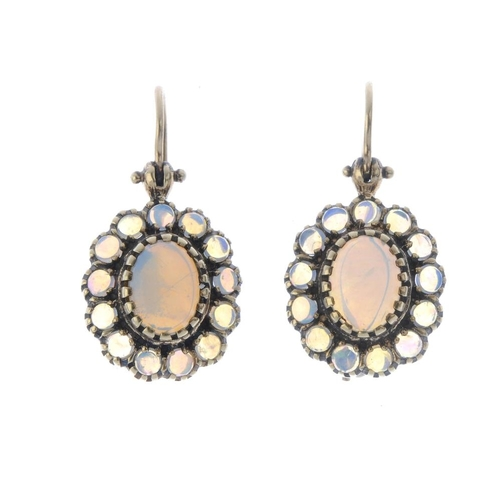 438 - A pair of opal earrings. Each designed as an oval opal cabochon, with circular opal cabochon surroun...