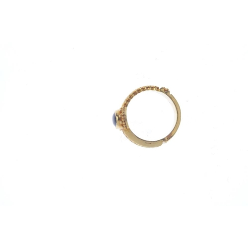 439 - A sapphire single-stone ring. The oval sapphire cabochon, with bead detail surround and asymmetric g...