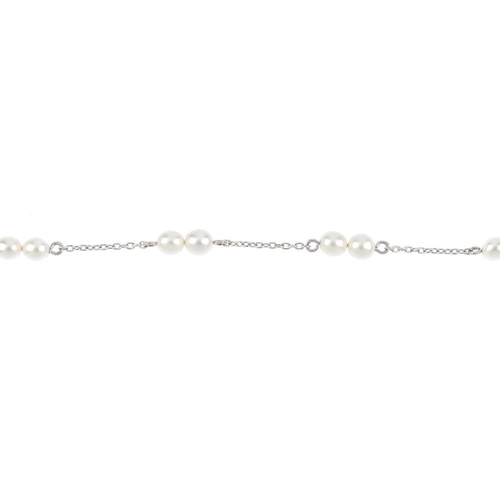 441 - A cultured pearl bracelet. Designed as a series of two cultured pearls, with trace-link chain spacer...