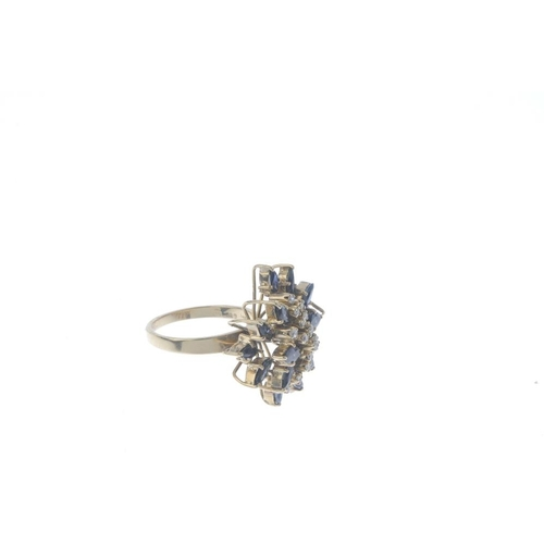 456 - A diamond and sapphire floral cluster ring. Designed as a series of single-cut diamond curved lines,...