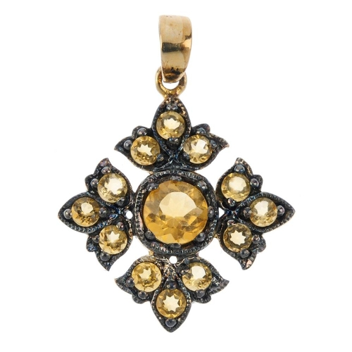 46 - A citrine pendant. The circular-shape citrine, within a similarly-cut citrine foliate surround. Leng...