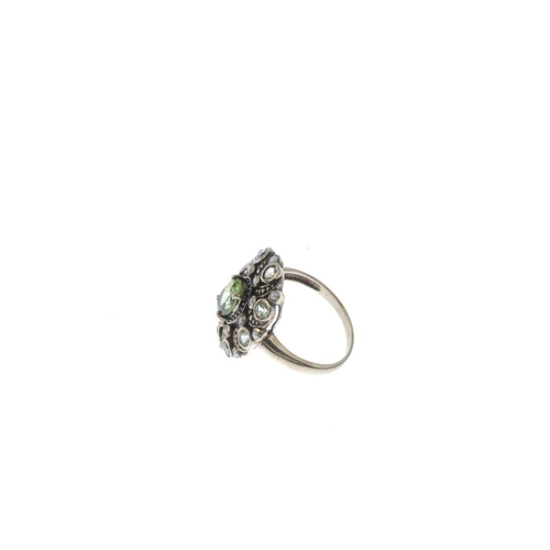 465 - A peridot and split pearl cluster ring. The oval-shape peridot, with split pearl and circular-shape ...