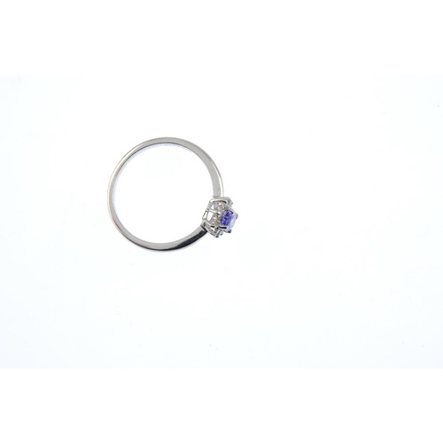 47 - A platinum tanzanite and diamond cluster ring. The oval-shape tanzanite, with brilliant-cut diamond ...