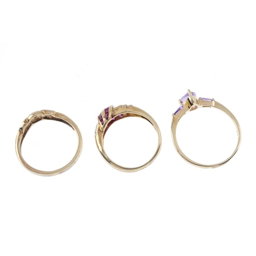 485 - Three gem-set rings. To include an amethyst three-stone ring, a ruby and diamond scrolling band ring...