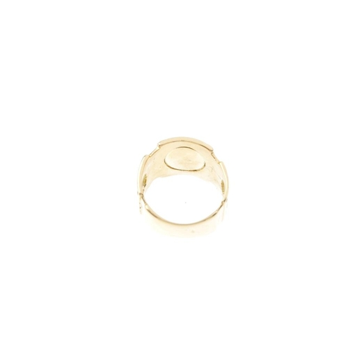 491 - An 18ct gold dress ring. The circular-shape cream panel, with a Greek key motif surround, dimple sid...