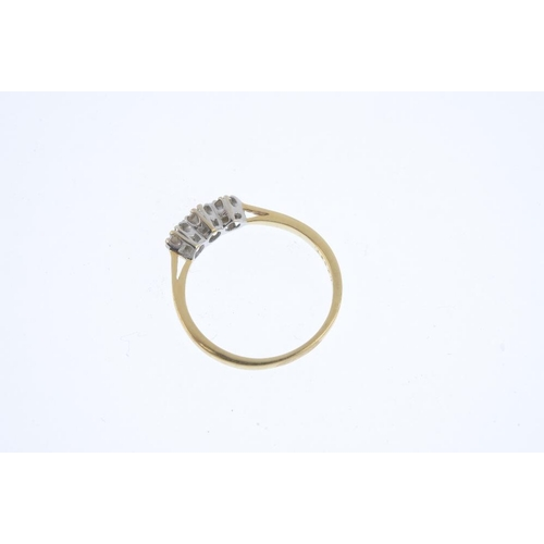 493 - An 18ct gold diamond three-stone ring. The graduated brilliant-cut diamond line, with tapered should...