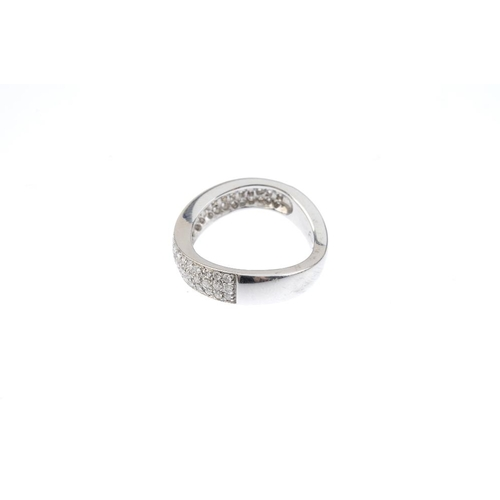 505 - A diamond dress ring. The pave-set diamond scrolling panel, with similarly designed scrolling plain ...