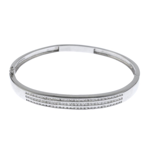 508 - A diamond hinged bangle. Designed as three brilliant-cut diamond lines, inset to the polished half-b...