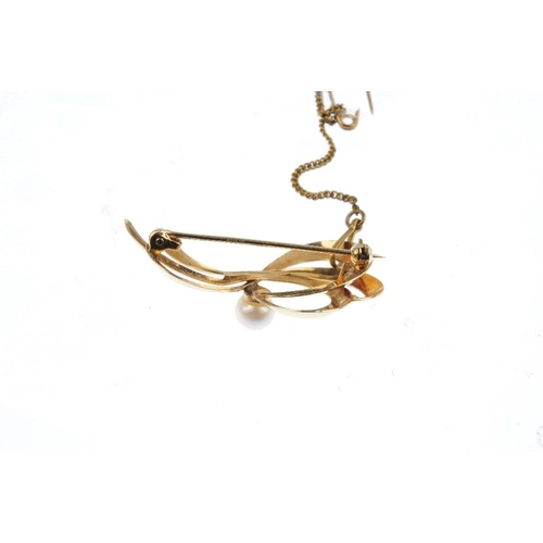 515 - A 9ct gold cultured pearl brooch. Designed as a cultured pearl, within a stylised ribbon openwork pa...