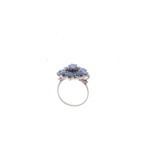 524 - A sapphire cluster ring. The oval-shape sapphire, within a similarly-cut sapphire surround. Ring siz...