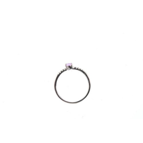 527 - An 18ct gold sapphire and diamond ring. The oval-shape pink sapphire, with brilliant-cut diamond sid...
