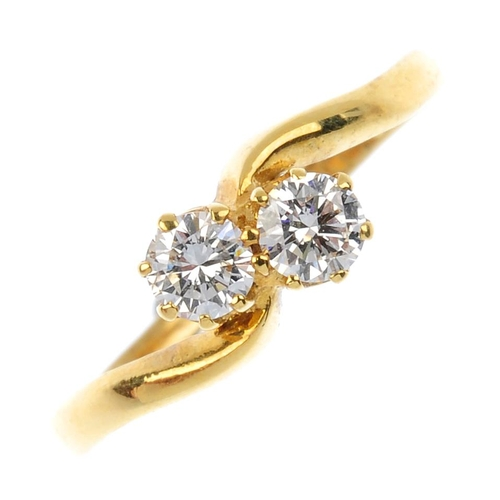 53 - An 18ct gold diamond crossover ring. The brilliant-cut diamond diagonal line, with asymmetric sides....