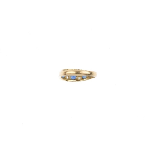 532 - An early 20th century 18ct gold sapphire and diamond ring. The vari-shape sapphire graduated line, w...