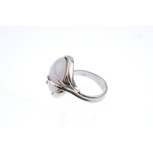 534 - A 1970s 18ct gold hardstone dress ring. The oval light purple cabochon, with crossover shoulders and...