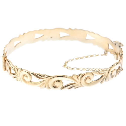 535 - A 9ct gold hinged bangle. Of openwork design, the repeating scrolling motif, with slide clasp. Hallm...