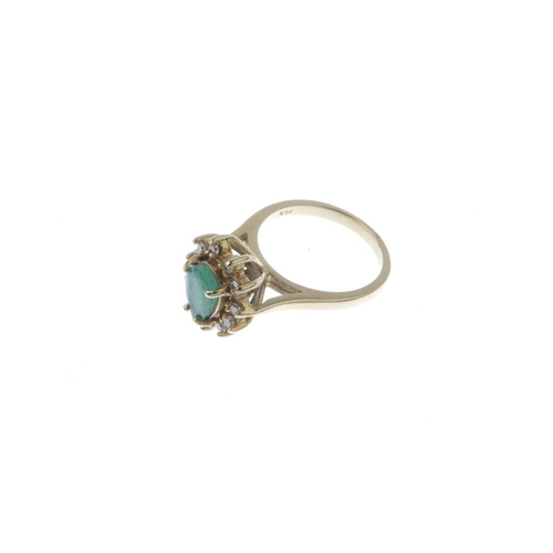 54 - An emerald and diamond cluster ring. The pear-shape emerald, within a brilliant-cut diamond surround...