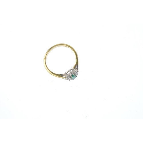 540 - An 18ct gold emerald and diamond cluster ring. The oval-shape emerald, within a brilliant-cut diamon...