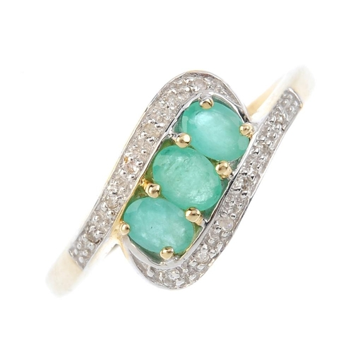 545 - A 9ct gold emerald and diamond crossover ring. Designed as a series of three oval-shape emeralds, wi...