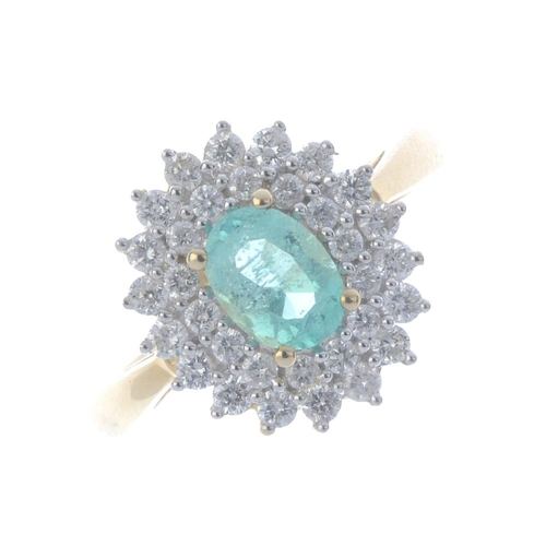 548 - A 14ct gold Colombian emerald and diamond cluster ring. The oval-shape Colombian emerald, within a b...