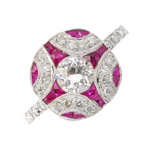 55 - A ruby and diamond dress ring. The circular-cut diamond, within a brilliant-cut diamond and calibre-...