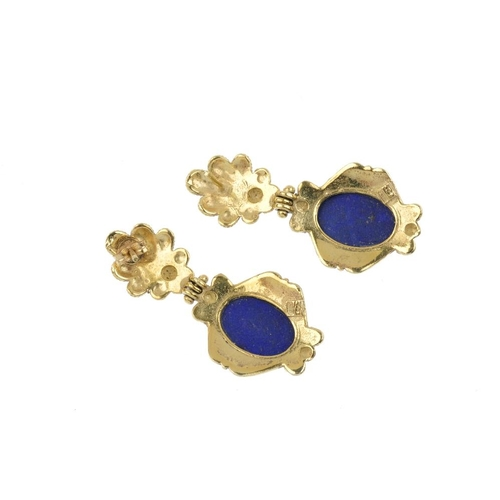 551 - A pair of lapis lazuli earrings. Each designed as an oval lapis-lazuli cabochon, within a rope-twist...